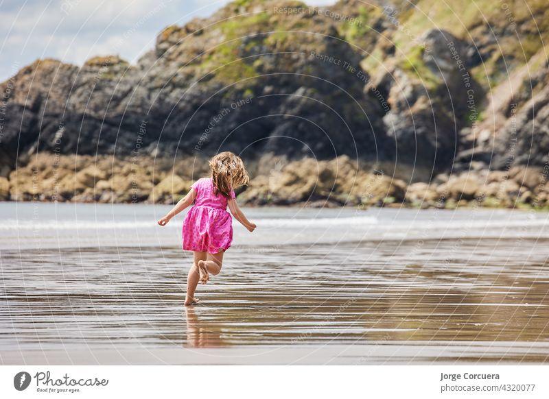 Hispanic Mädchen läuft entlang des Strandes mit großen Felsen im Hintergrund Sand Spielen bezaubernd Kleinkind Kind Sommer jung Kindheit MEER Person niedlich