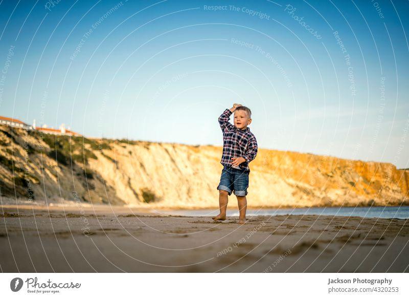 Kleiner Junge wirft Steine am Strand bei Sonnenuntergang spielen Kleinkind Textfreiraum Sagres Portugal Barfuß Sohn horizontal Baby sonnig laufen Seeküste