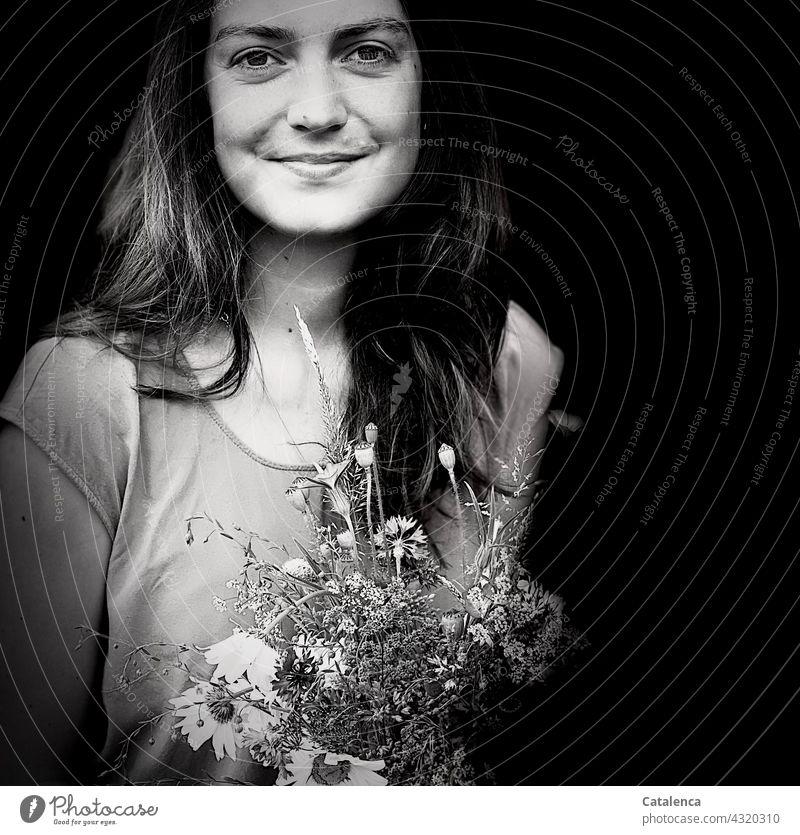 Lächelnde, junge Frau hält einen Wiesenblumenstrauß Natur Flora Person weiblich Blumen Pflanze schauen Blüte duften verblühen Blumenstrauß Margariten Kornblumen