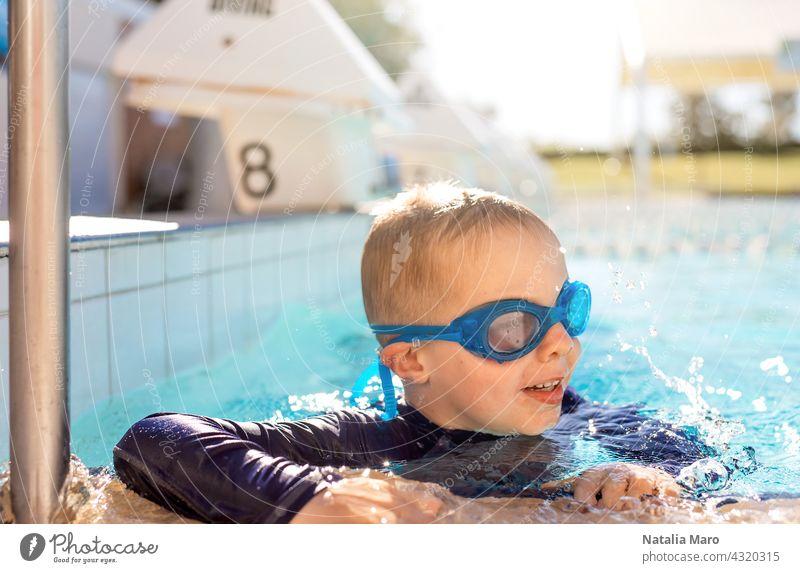 Kind mit Schwimmbrille im Schwimmbad Pool blau Junge Urlaub schwimmen Wasser im Freien Sommer Schutzbrille Glück Freude Lächeln nass Erholung spielen Freizeit