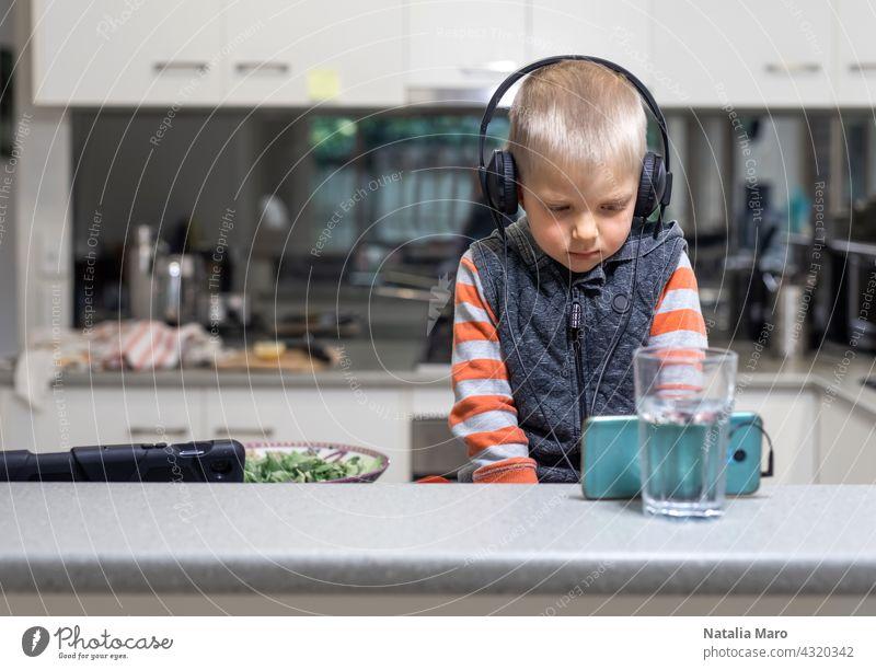 Kleines Kind Junge wares Kopfhörer und spielen das Handy auf dem Küchentisch Computer Sohn Tablette studierend Koch Haus Internet Technik & Technologie