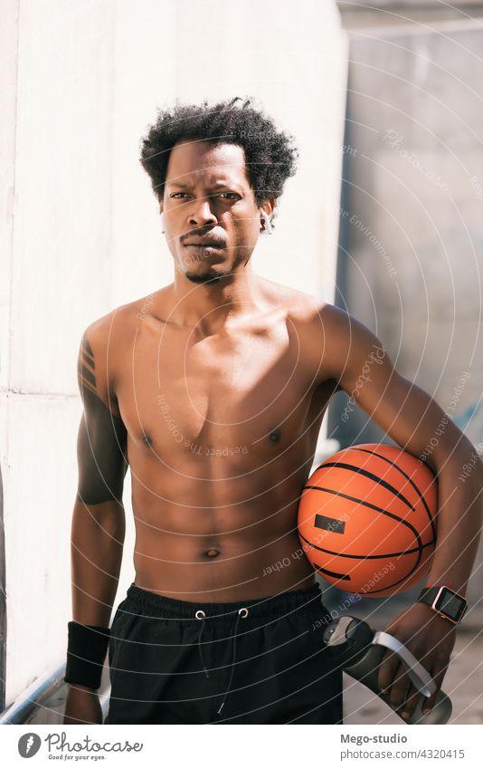 Afro-Athlet Mann hält einen Basketball-Ball im Freien. Sport urban sportlich Stehen genießen Ausdruck aktiv Hand Übung Erholung Fitness Training Blick Aktivität
