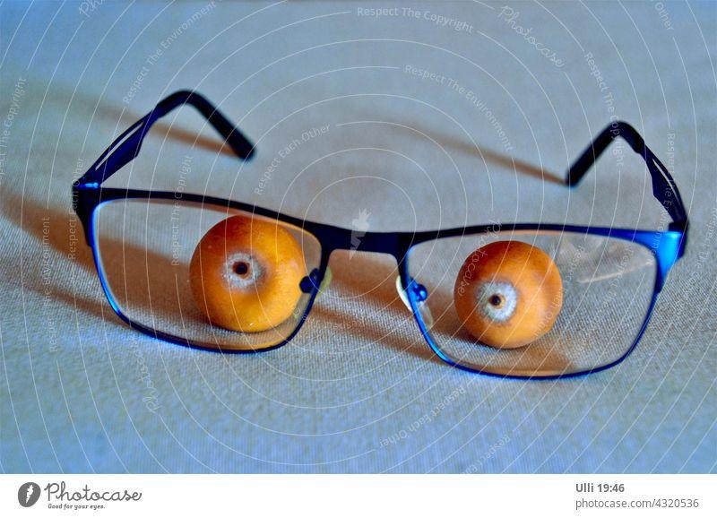 Palmenfrüchtchen mit Lesebrille. Tischdekoration Brille Palmenfrüchte Tischdecke lustige Action lustige Idee Augen blaue Brille orange Pupille Dekoration Scherz
