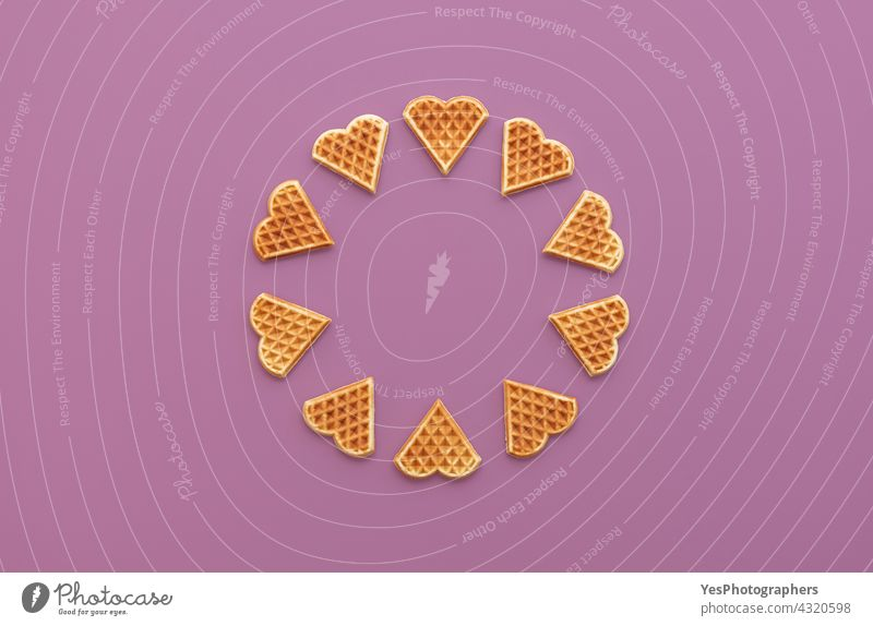 Herzförmige Waffeln in der Draufsicht auf einem lila Hintergrund oben ausgerichtet angeordnet gebacken Bäckerei Belgier Belgien Frühstück kreisen Farbe