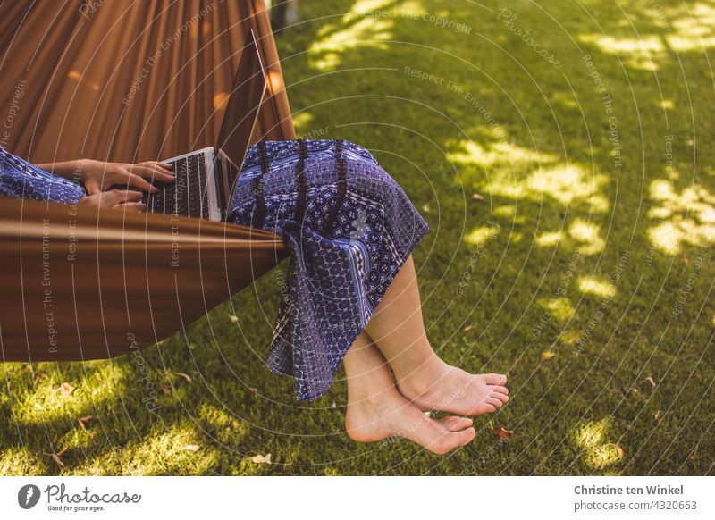 Eine junge Frau im blauen Sommerkleid sitzt gemütlich in einer Hängematte im Garten, arbeitet am Notebook und lässt die Füße baumeln laptop Computer Homeoffice