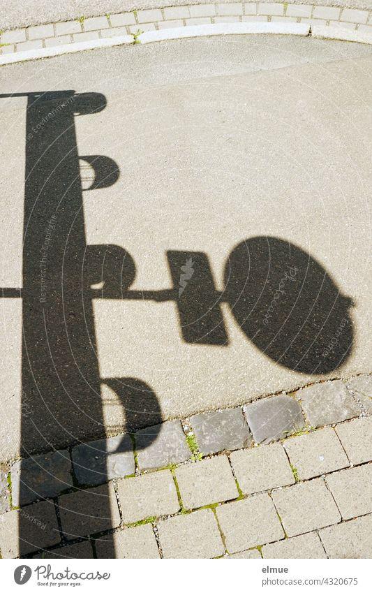Schatten eines Verkehrszeichens und einer Verkehrsbake auf einem Fußweg / Absperrung / Gefahrenstelle verboten für Fußgänger verboten Absperrgitter Vorschrift