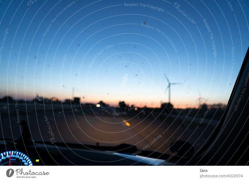 Autofahrt zur blauen Stunde blaue Stunde Dämmerung Abend Sonnenuntergang Licht Farbfoto Windrad Tacho Windschutzscheibe