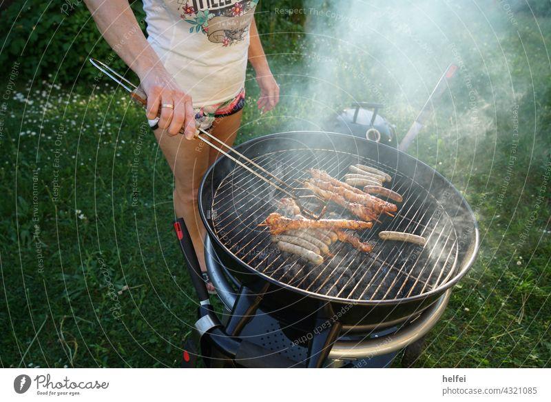 Grillen am Holzkohlengrill mit Bratwürsten und rauchenden Holzkohlen Grillsaison Kugelgrill Grillplatz Feuer Sommer Essen Glut Grillkohle Rauch gegrillt
