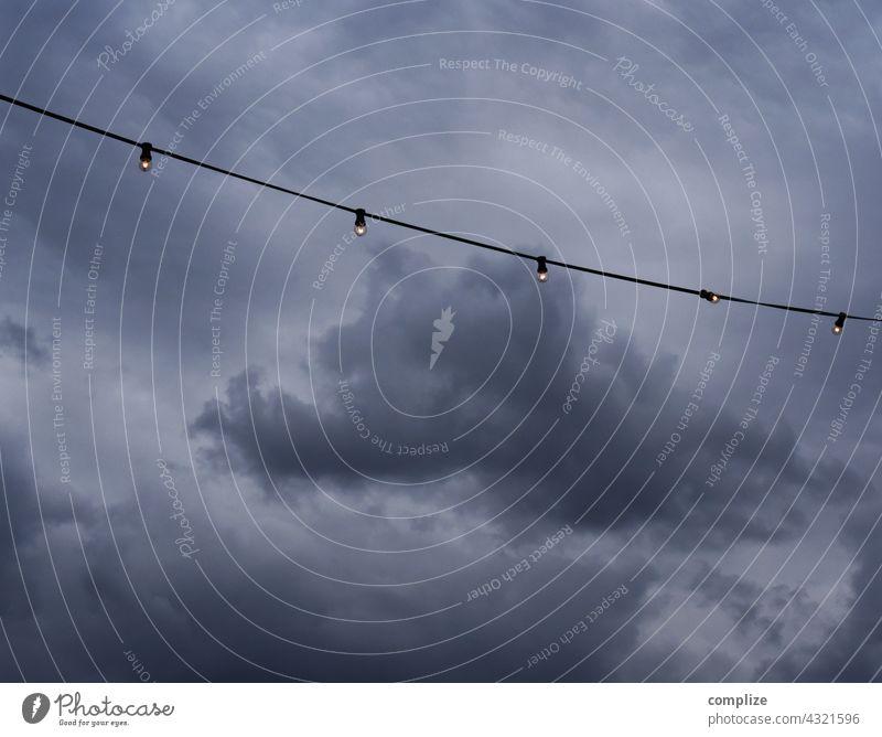 Lichterkette vor dunkelen Gewitterwolken Unwetter Starkregen Unheil Gastronomie Biergarten pandemie Wolken Wetter Klima Klimawandel