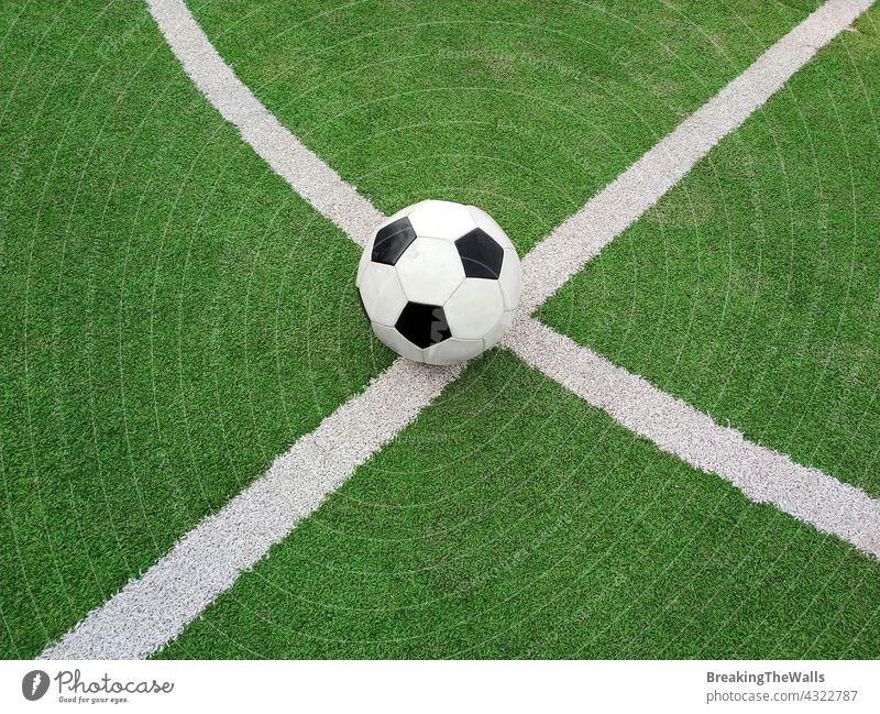 Fußball Ball über grünem Fußballfeld schwarz weiß Feld Platz Rasen künstlich Nahaufnahme Markierung Linie Sport spielen Spiel niemand keine Menschen