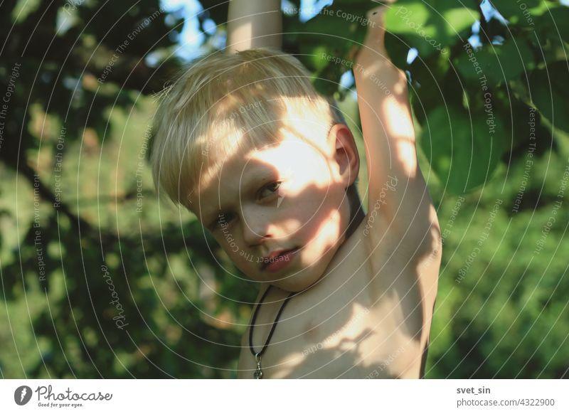 Ein blonder kleiner Junge mit einem orthodoxen Kreuz auf der Brust hängt an einem Apfelbaum, hält sich an einem Ast fest, in einem sonnigen Sommergarten. Glückliche Kindheit auf dem Dorf. Porträt eines blonden Jungen mit Sonnenblendung auf der Haut.