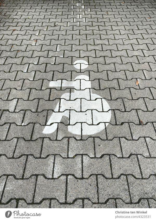Rollstuhlfahrer Symbol auf einem gepflasterten Parkplatz, Behindertenparkplatz, Gehbehinderung Piktogramm Behindertengerecht Gehbehindert