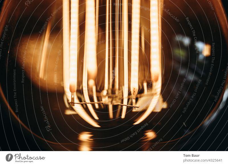 Nahaufnahme einer Glühbirne - die Drähte glühen erleuchten gelb Led Objektfotografie Bokeh-Effekt bokeh lichter Bokeh Hintergrund Hintergund Draht Design