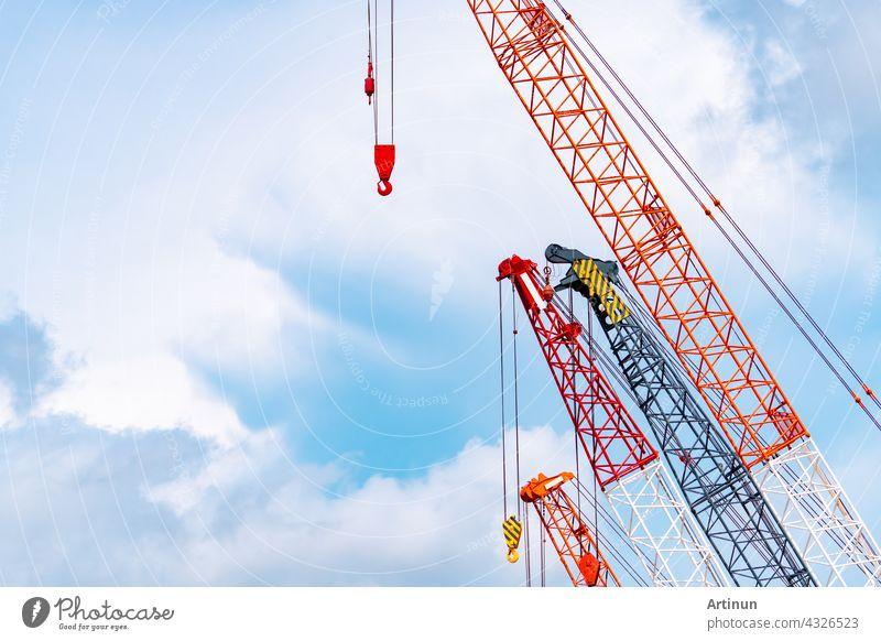Raupenkran gegen blauen Himmel und weiße Wolken. Immobilien-Industrie. Red Raupenkran Verwendung Haspel heben Ausrüstung in Baustelle. Kran zu vermieten. Kran-Händler für Baugeschäft.