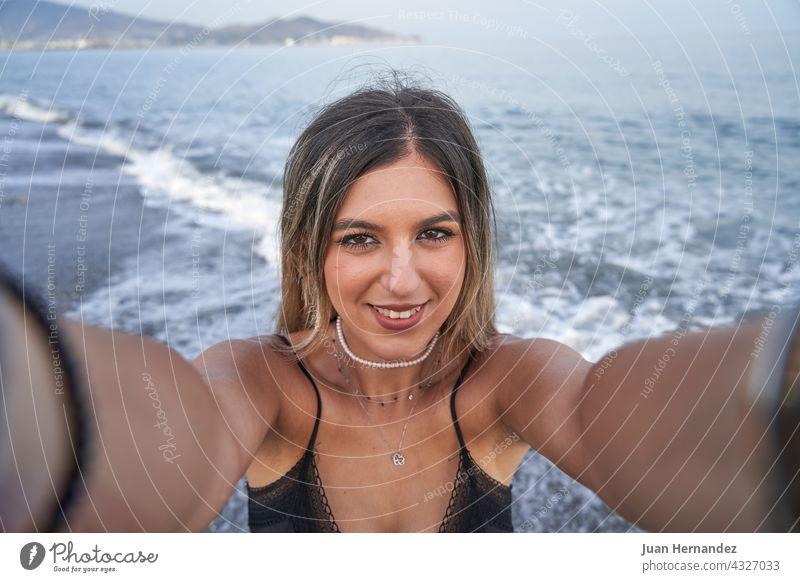 junge Frau nimmt ein Selfie mit dem Handy und das Meer im Hintergrund hübsch Mobile MEER Smartphone Foto Bild Dame Lächeln Nizza Schönheit posierend Telefon