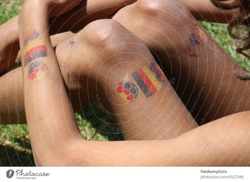Kinder-Tattoos mit deutschem Fußball-Motiv auf Armen und Beinen eines Mädchen tätowiert Nationalität WM EM Deutschland Deutschlandfahne