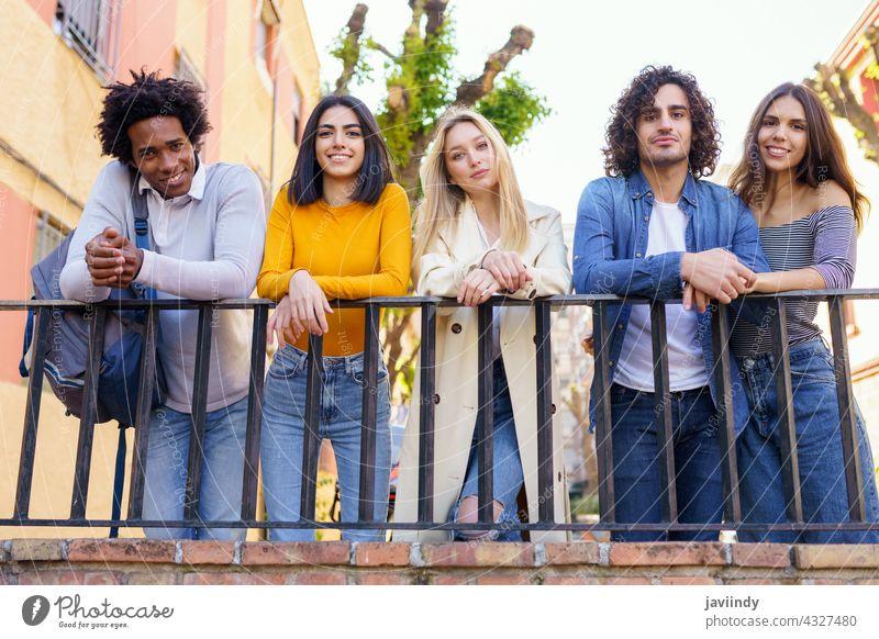 Multirassische Gruppe von jungen Leuten, die sich auf der Straße unterhalten. Menschengruppe Schüler multiethnisch sozialisierend Vielfalt Freunde