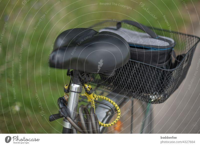ein auf dem Radweg parkendes Fahrrad mit Blick auf den Sattel und den Fahrradkorb, in dem sich eine Kameratasche befindet Fahrradtour Fotosafari