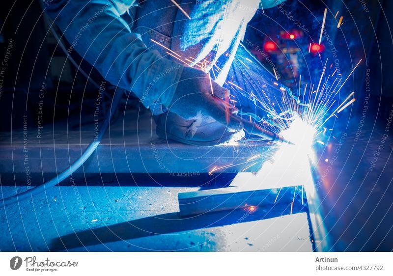 Schweißer schweißt Metall mit Argon-Lichtbogen-Schweißgerät und hat Schweißfunken. Ein Mann trägt Schutzhandschuhe. Sicherheit am industriellen Arbeitsplatz. Schweißer arbeitet mit Sicherheit. Arbeiter in der Stahlindustrie Fabrik.