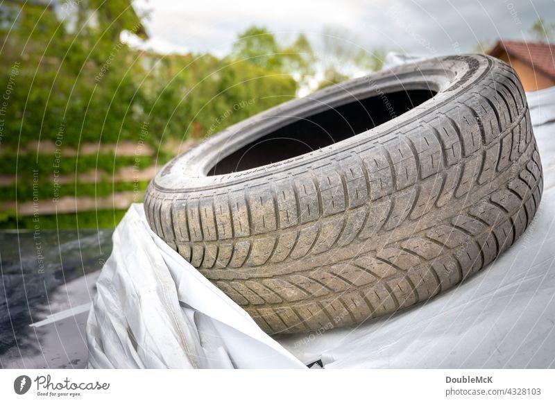 Dreckiger Autoreifen liegt auf Autoplane dreckig PKW Fahrzeug Verkehrsmittel Straßenverkehr Autofahren Farbfoto Außenaufnahme Menschenleer Tag Mobilität kaputt