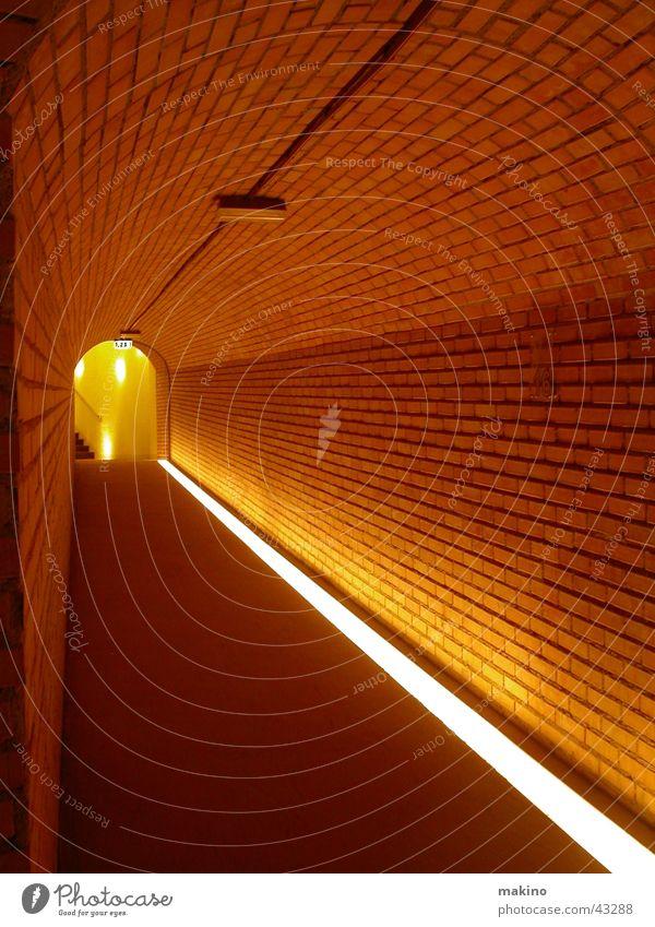 den Gang entlang... (2) Licht rot Backstein Linie Tunnel Wand Architektur Stein Bodenbelag Flur leer Menschenleer Zentralperspektive Fluchtlinie Fluchtpunkt