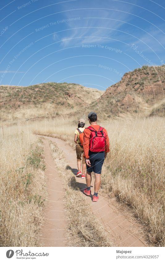 Kaukasisches Paar 40-50, von hinten gesehen, beim Wandern in der Natur im Sommer. El Cerro Park, Alcala de Henares, Madrid, Spanien, Europa Verschlussdeckel