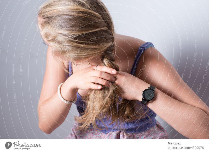 Blondes Mädchen, das ihr Haar mit den Händen zu einem Zopf ordnet. Anonyme Person. anonym blond arrangierend Kämmen Behaarung langhaarig Bräune Ring Sommer