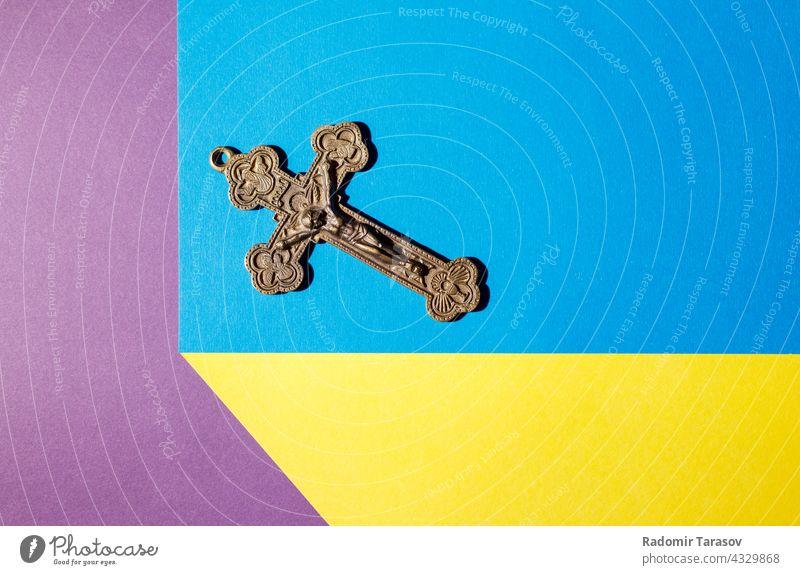 Bronzekreuz auf dem farbigen Tisch durchkreuzen alt Christentum Kruzifix Jesus religiös christian Christus Religion Gott Symbol Glaube geistig Metall