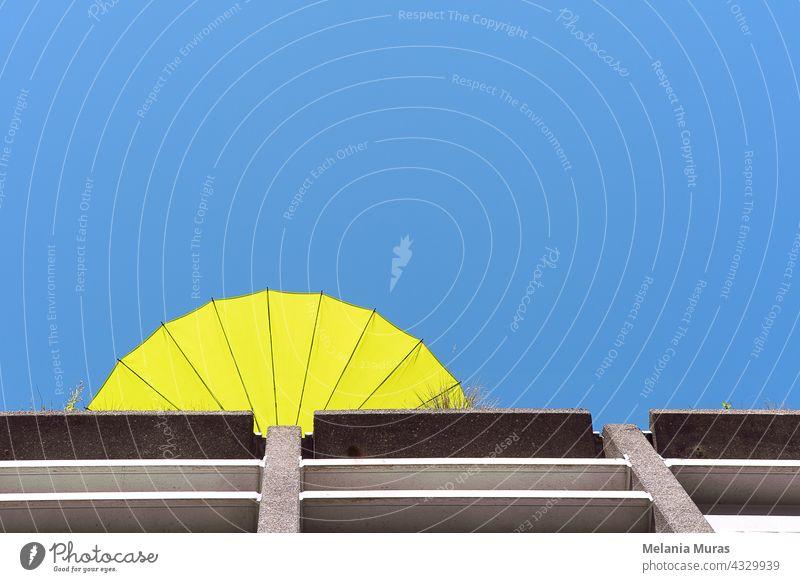 Abstrakte Architektur, gelber Sonnenschirm auf der Dachterrasse, Sommerstimmung, Ansicht von unten. Blauer Himmel abstrakt Architekturabstrakt Hintergrund schön