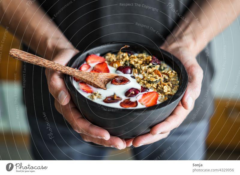 Mann hält eine Schüssel mit Granola, Joghurt und Erdbeeren in den Händen Frühstück halten teilabschnitt Müsli Gesundheit geröstet Nuss Vintage Holz Diät Löffel