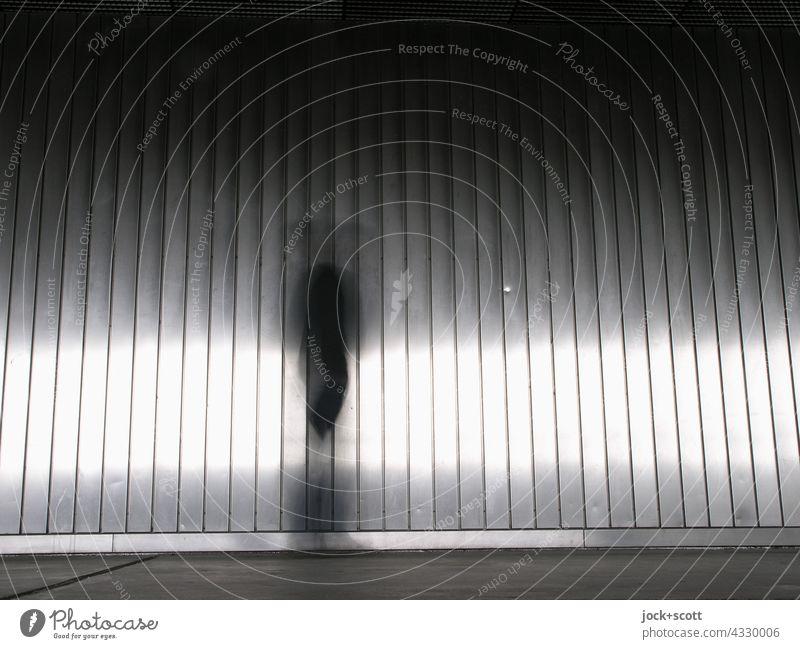 Erscheinung vor einer Metallwand Wand modern urban Aluminium Vorschein Bewegungsunschärfe Lichtreflexe Silhouette Strukturen & Formen Streifen anonym
