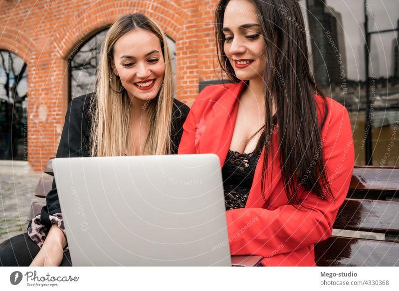 Zwei junge Freunde benutzen einen Laptop im Freien. zwei Computer Mädchen Notebook Freizeit Gerät freudig pc Anschluss Genuss Zwei Personen Gespräch online