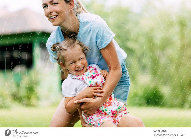 Eine junge Mutter und ihr süßes kleines Mädchen haben Spaß in einem sonnigen Garten. Das Konzept einer glücklichen Kindheit und Mutterschaft Baby Glück Mama