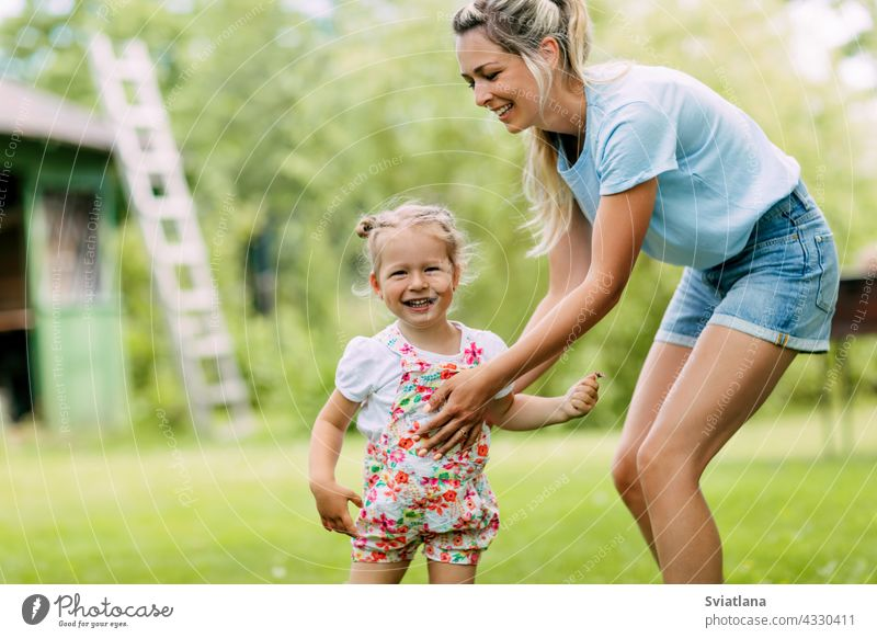 Die Mutter und ihre kleine Tochter spielen im Freien. Das Konzept einer glücklichen Kindheit und Mutterschaft Baby Spaß Glück Garten Mama niedlich jung Mädchen