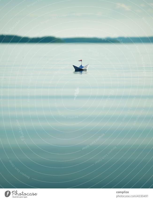 Ruhiger See mit kleinem Papierschiff Freiheit Sonnenstrahlen Sonnenlicht Küste Segelboot Ziel Schifffahrt Kindheit Strand Sommerurlaub Wasser Natur Umwelt