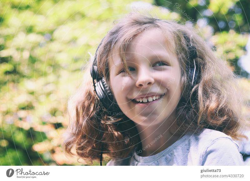 Porträt eines lachenden 10jährigen Jungen mit langen, lockigen Haaren und Kopfhöhrern 10 Jahre 11 Jahre draußen Schönes Wetter Fröhlichkeit lustig