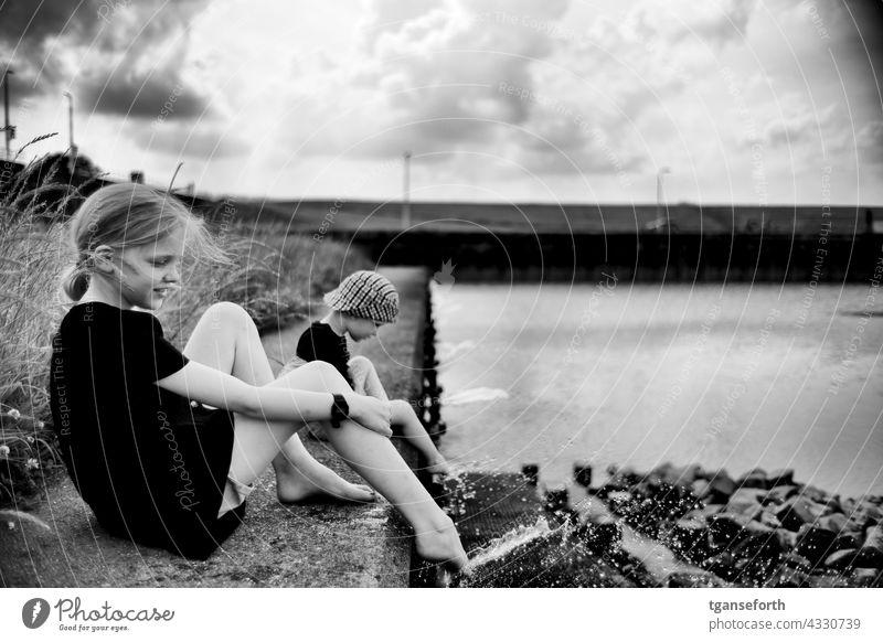 Kinder am Wasser abkühlung spritzen Füße kühlen Kaimauer Dollart Wassertropfen Erfrischung Schwimmen & Baden nass Sommer Außenaufnahme Kühlung Freude Spaß spiel