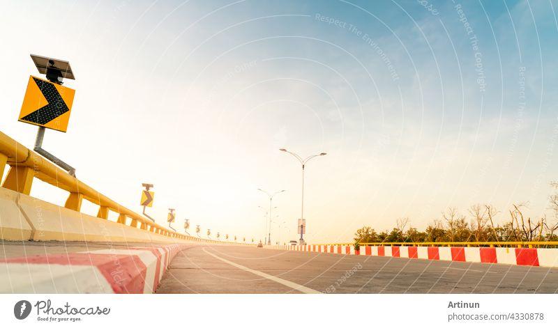 Kurve Betonstraße mit Kurve Verkehrszeichen neben dem Meer bei Sonnenuntergang Zeit. Sonnenkollektor Energie auf gelbe Kurve Verkehrszeichen. Road Trip im Sommerurlaub. Blur Autofahren. Sommer Reise mit dem Auto.