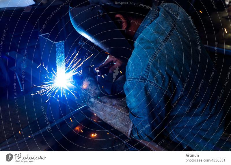 Schweißer schweißt Metall mit Argon-Lichtbogen-Schweißgerät und hat Schweißfunken. Ein Mann trägt eine Schweißmaske und Schutzhandschuhe. Sicherheit am industriellen Arbeitsplatz. Schweißer arbeitet mit Sicherheit. Stahlindustrie.