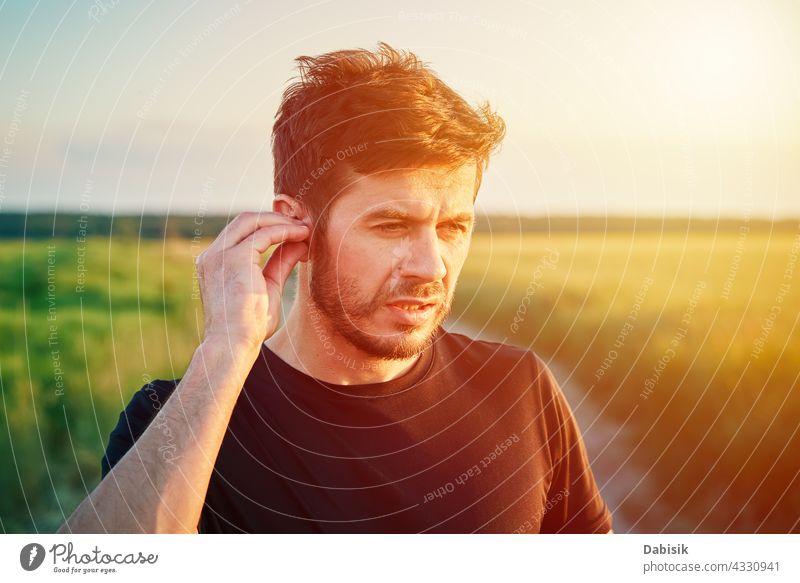 Aktive Millenial Mann Porträt im Freien bei Sonnenuntergang Sport Kaukasier Lifestyle Athlet Fitness Generation Kopfhörer Vollbart lässig Übung passen außerhalb
