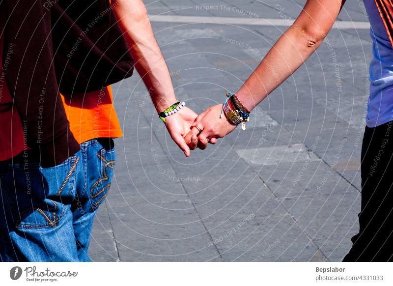 Liebende, die sich an den Händen halten Händchenhalten Liebespaar Lieblinge Hand für Hand junge Leute Armbänder Familie Nachbarn Freundinnen Kaukasier