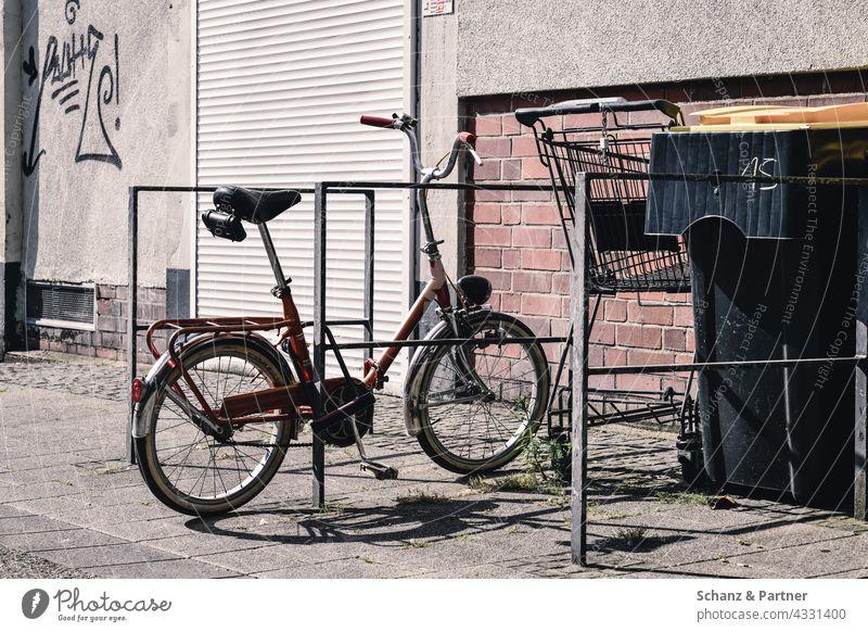 altes Klapprad am Fahrradständer Klappfahrrad Verkehrswende Stadtleben Einkaufswagen Mülltonne Rolladen Schatten