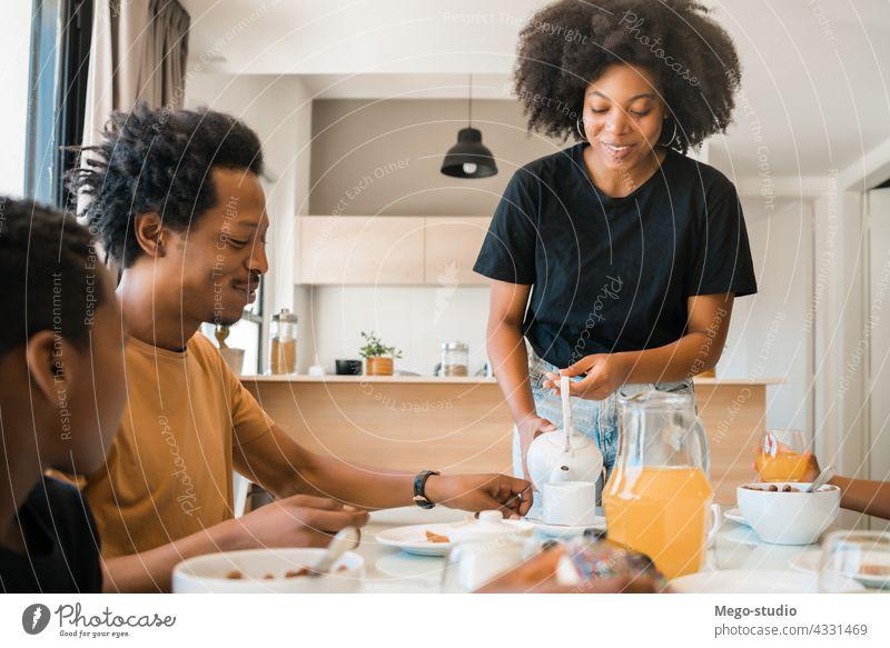 Familie beim gemeinsamen Frühstück zu Hause. Morgen Zusammensein Kind niedlich Gesundheit Lebensmittel Servieren gemischtrassig Afroamerikaner Person heimisch