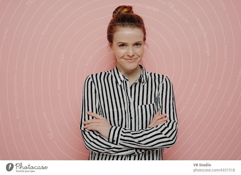 Happy Teenager-Mädchen mit verschränkten Armen posiert gegen rosa Studio Hintergrund zufrieden Glück Rotschopf Frau Behaarung Brötchen Blick gerade Lächeln