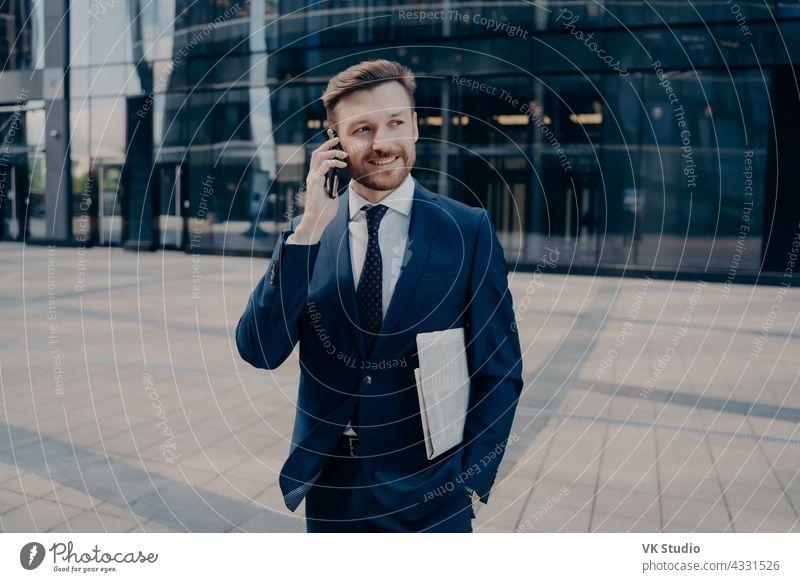 Glückliche Büroangestellte mit Zeitung im Gespräch auf Smartphone gutaussehend Geschäftsmann Telefon Mobile Anruf Lächeln männlich Nachrichten blau