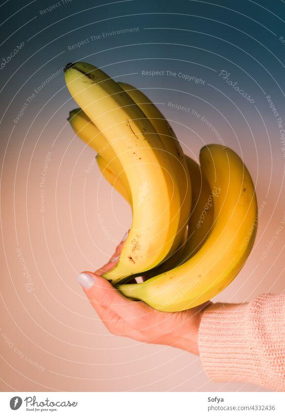 Bündel Bananen in der Hand einer Frau. Farbe Kunst Haufen nageln Lebensmittel Design modern Trends Diät Mode Maniküre Licht Korallen Frucht Mädchen Ernährung
