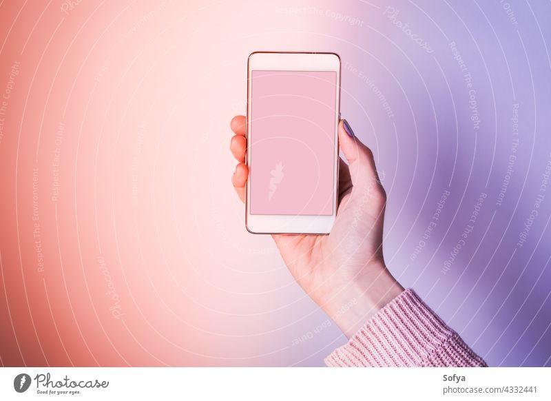 Hand mit Handy-Bildschirm auf rosa und lila Mobile Telefon Hintergrund violett Smartphone Gerät purpur ultra Korallen Frau Textfreiraum Einladung Anwendung
