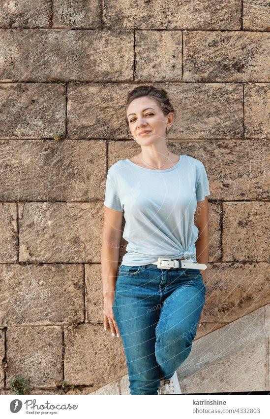 Frauen in T-Shirt und Jeans bleiben in der Nähe einer Wand Erwachsener mittleres Alter Lächeln lässig Attrappe im Freien blondhaarig Jahrtausende Textfreiraum