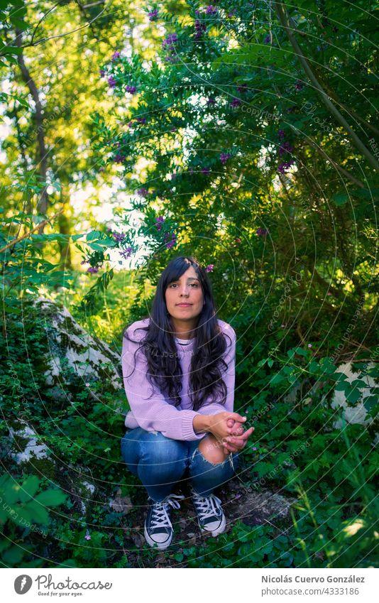 Junge Frau sitzt auf einem Felsen, umgeben von Bäumen und Pflanzen Person Gras Natur Erholung grün Porträt Lächeln Fröhlichkeit Glück im Freien Lifestyle