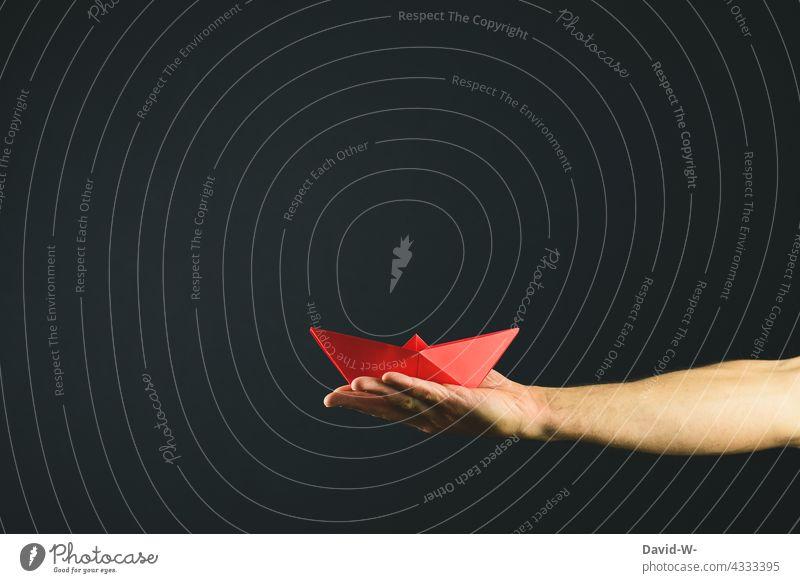 Schiff aus Papier in einer Hand - Konzept - Führung / Freiheit / reisen Papierschiff freiheit Erfolg Reisen Erfolgskonzept Erfolgsaussicht Papierboot Urlaub